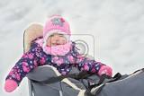 Fotografie cute little girl sitting on her sledge in winter day