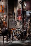 Fotografie still life with violins cello cases and wheels in rural style