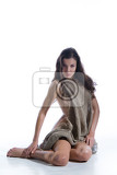 young woman in a piece of fabric on isolated studio background