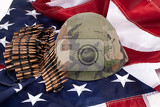 Fotografia band with cartdidges and army helmet on an american flag