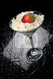 Fényképek strawberries and whipped cream on a black glass background