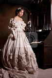 Fotografie young beautiful woman in a wedding dress standing near the old secretaire