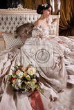 Fotografie young beautiful woman in a wedding dress sitting on a bed