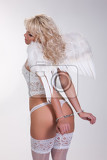 young woman in white lingerie with angel wings and handcuffs