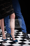 Fotografie womans and mans legs in dancing poses on a checkered background