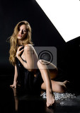Fotografia young nude woman on a black mirror background
