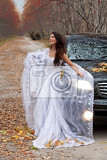 Fotografia young woman in a wedding dress standing near the jeep in an autumn forest