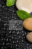 Fotografie pebble stones and green leaf with water drop zen stone on black background spa tranquil scene concept with reflection backdrop