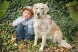 Fotografia little cute boy playing with his dog in the park