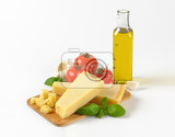Fotografie still life of parmesan cheese vegetables and bottle of olive oil on white background