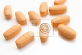 macro of orange pills isolated on white background
