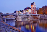The building with the bridge over the river at dusk.Hucak in Hradec Kralove