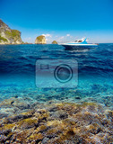 underwater and surface split view in the tropics paradise with yacht fish and coral reef above waterline beautiful view on tropical island nusa penida bali indonesia holiday vacation concept