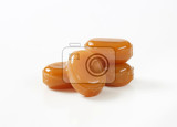 four caramel candies on white background
