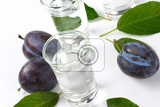 plum brandy slivovitz in shot glasses and fresh damson plums
