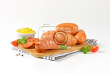Fotografia raw and roasted sausages on cutting board and bowl of mustard