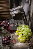 grape and glass of wine on an old wooden desk
