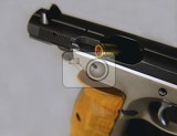 Fényképek shell casings flying out the open end of a silver and black handgun