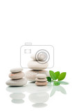 pile of balancing pebble stones and green leaf like zen stone isolated on white background spa welness tranquil scene concept with reflection