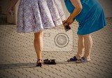 mother on slippered  fastens the shoe of his daughter