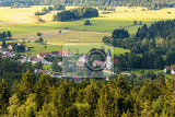Fotografie aerial view from lookout u jakuba to czech landscape known as czech canada touristic place view to forest field meadows and small village with rural church in sunny day with blue sky