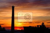 Fotografie factory chimney with the storks on nest at sunset