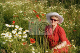 the elderly woman sitting in a meadow with poppies and chamomiles