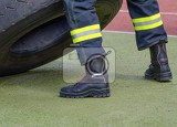 look at the legs of a fireman in protective boots and pants with reflective tapes