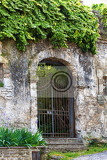 Fotografia gated arched entrance in a weathered wall in the tuscan village of bagni san filippo italy