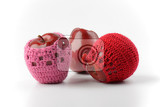 three red apples two of them in crochet cozies