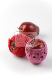 Fotografie three red apples two of them in crochet cozies