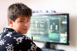 Fotografie teenager boy using computer at home with play online game in his child room
