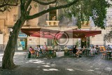 Fotografia catania sicily italy  june 25 2016 people sitting on the street in the shade under a large tree at the outdoor restaurant