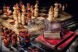 Photo wooden crafted chess old books and glass of tea