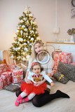 family with her daughter at christmas tree