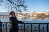 beautiful woman in prague embankment on river vltava in background st vitus cathedral and prague castle
