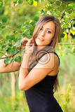 Photo portrait of smiling and charming lady woman girl outdoor with green background and black dress