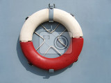 red and white lifebuoy ring hanging on a wall