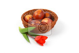 Fotografie basket of easter eggs decorated with fresh leaves and boiled in onion peels and tulip on white background