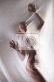 young nude woman behind the transparent fabric on a studio background