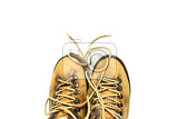 Fényképek yellow shoes with untied shoelaces on white background