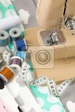 Fotografie sewing machine cotton fabric and tailor measurement tape with spools of thread cotton