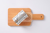 closed silver can on wooden cutting board