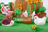 detail of birthday cake with farm marzipan animals and number 3