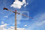 Photo crane on construction with blue sky clouds and sun in the background