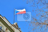 Fotografie the flag of the czech republic on a building with blue sky and the sun in the background