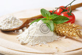 pile of wheat flour ripe tomatoes and fresh basil on wooden cutting board