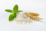 pile of wheat flour wheat ears and basil on white background