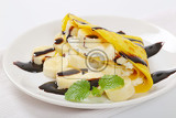 Fotografie crepes with slices of banana whipped cream and chocolate sauce