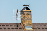 chimney from bricks in the house and tv antenna